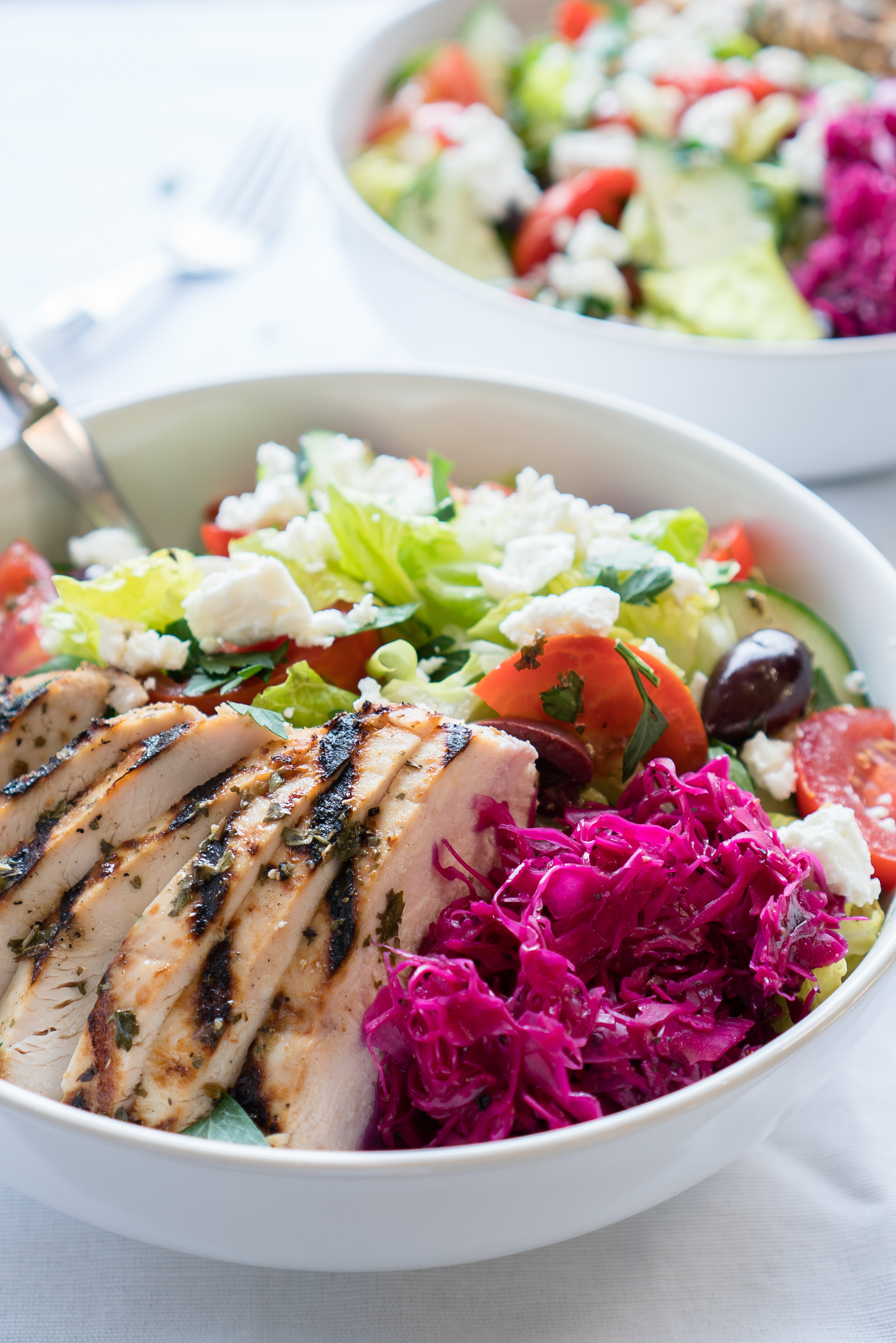 Mediterranean Salad Bowls – Simple, healthy recipe for Mediterranean Salad Bowls! Crisp romaine topped with cucumber, tomatoes, Kalamata olives, feta cheese, and homemade pickled red cabbage with a lemony Greek Dressing. Gluten-free & low carb! ♥ | freeyourfork.com