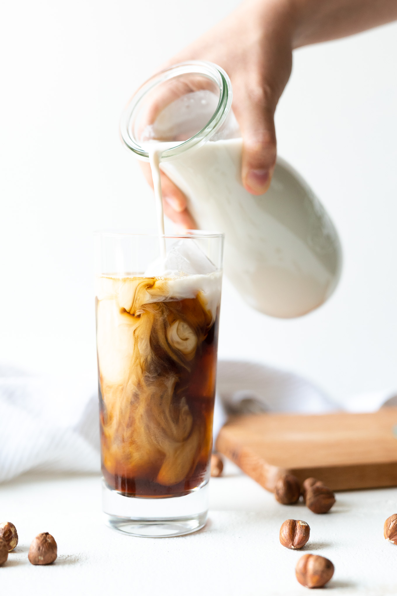 Pouring hazelnut milk into iced coffee in tall glass