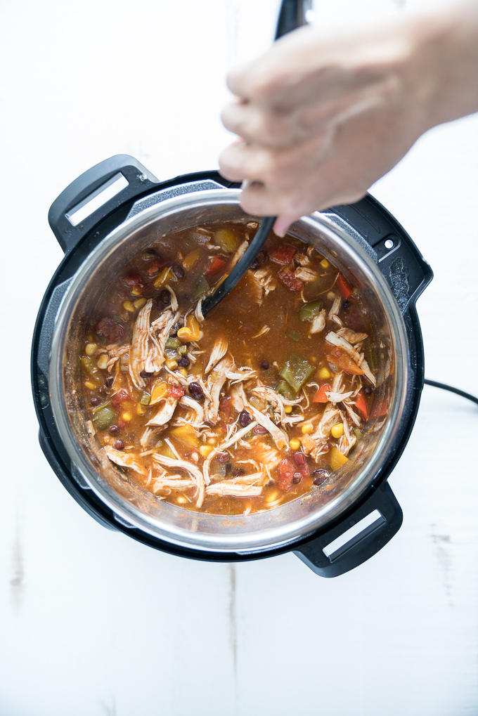 Chicken Tortilla Soup - Healthy recipe made in the instant pot using lean chicken breast, black beans, tomatoes, bell peppers, green chiles, jalapeño, corn, and more. Best served with toppings like sour cream + avocado + crisped tortilla strips! ♥ | freeyourfork.com