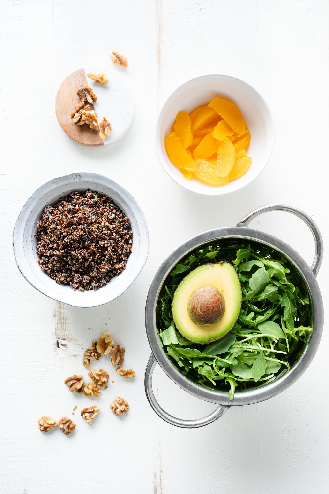 arugula avocado oranges quinoa walnuts on white table