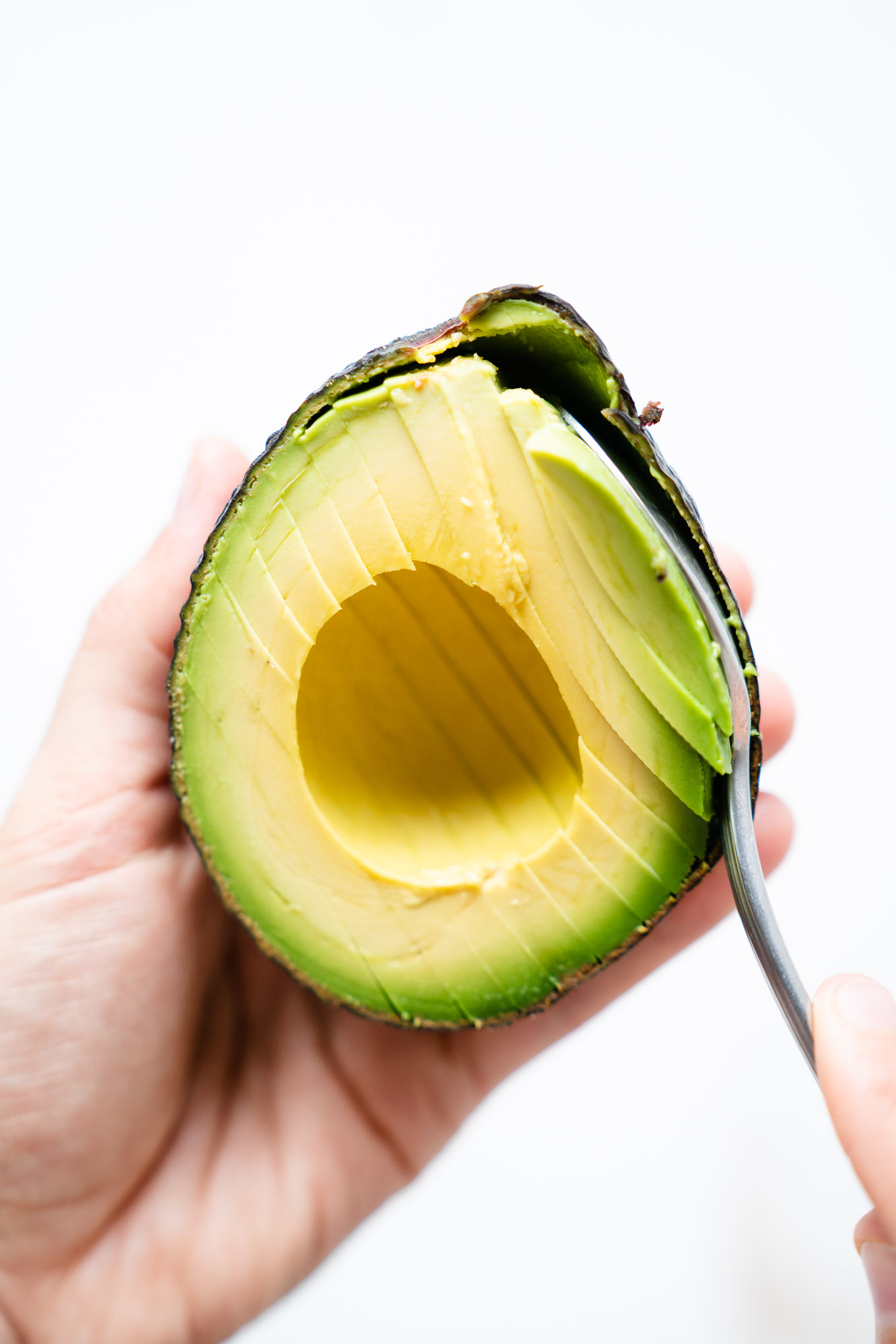 Avocado slices being scooped out with a spoon