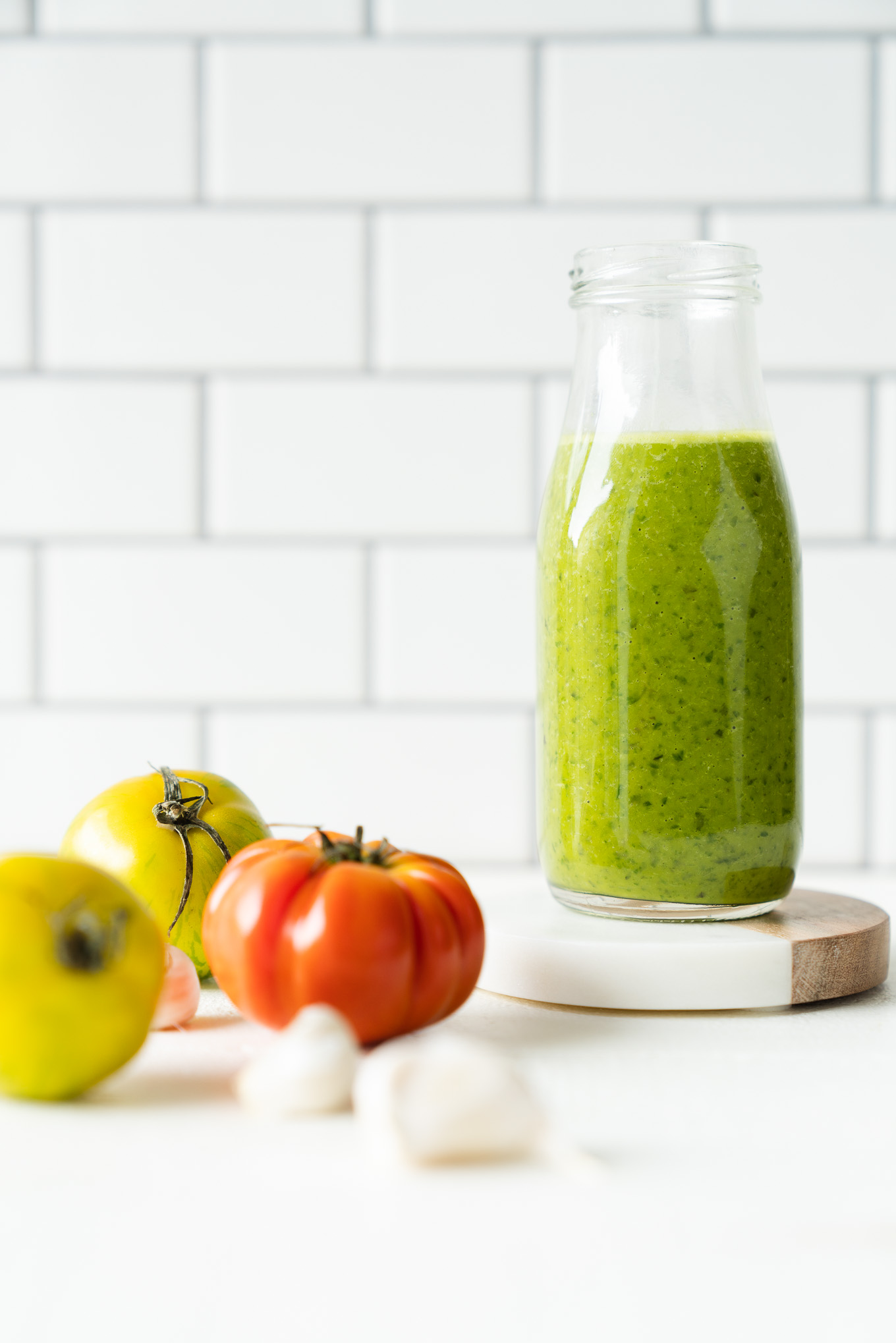 Basil Vinaigrette in glass jar with tomatoes