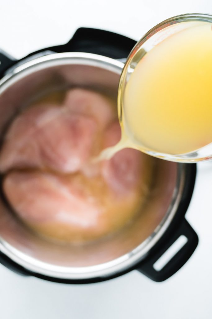 pouring broth over instant pot filled with chicken