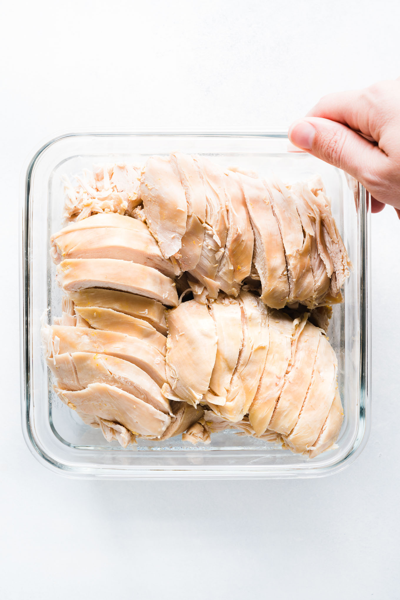 Sliced chicken breast in glass square container