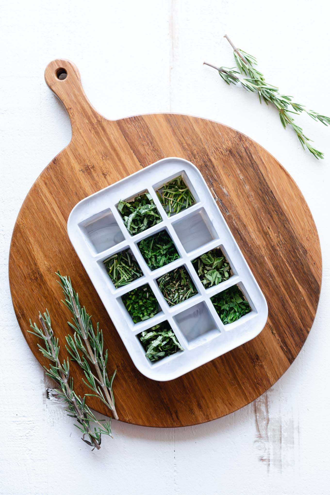 Chopped herbs in white ice cube tray on brown cutting board