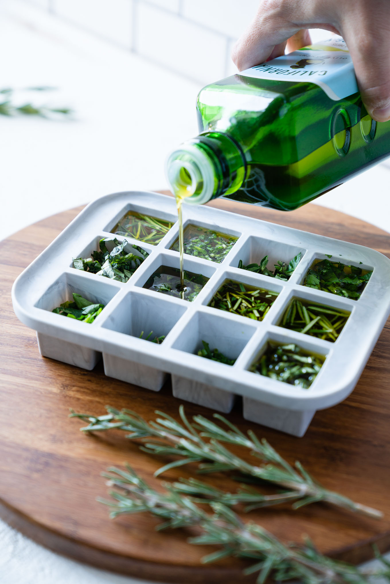 Olive oil being poured into ice cube tray over herbs