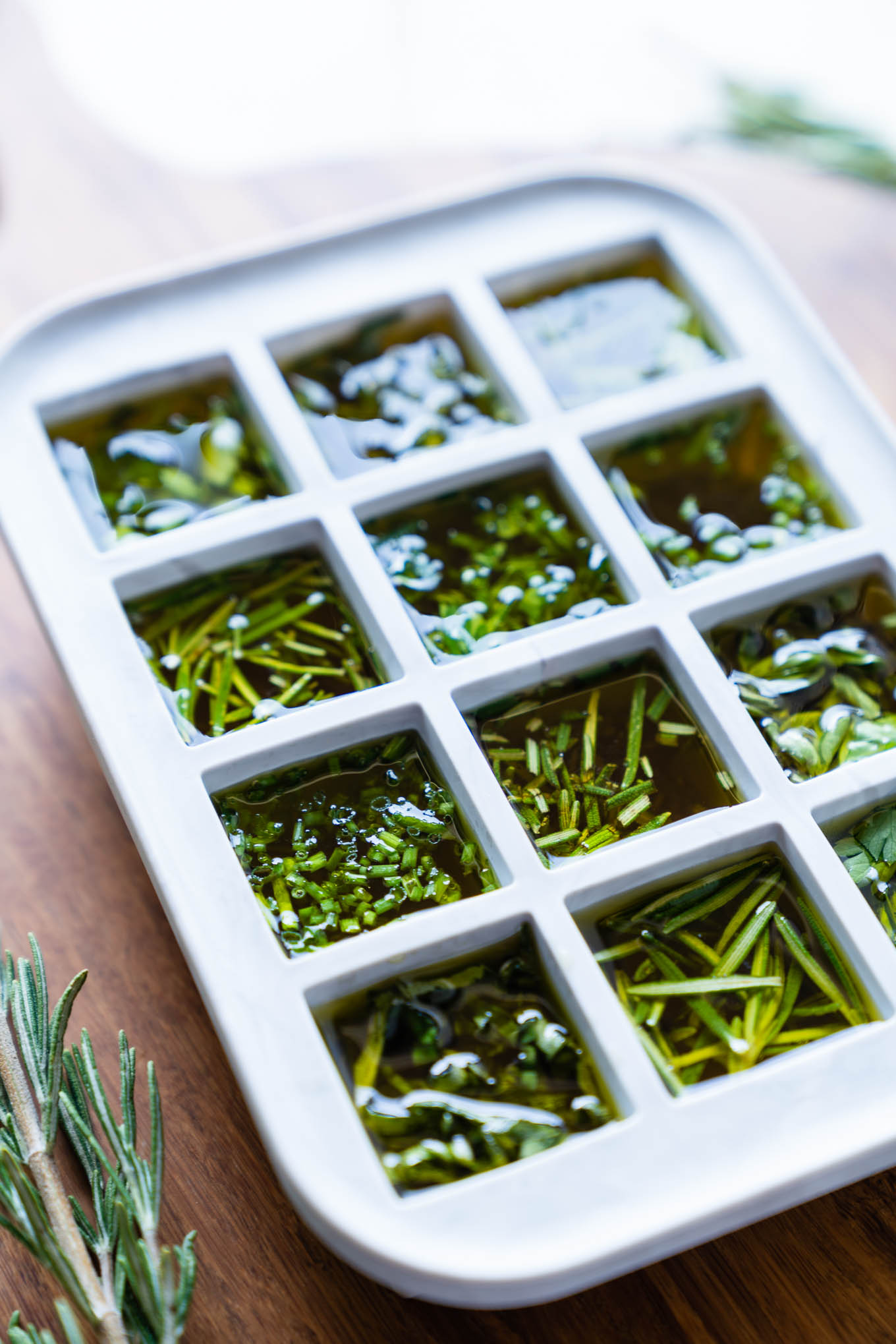 Ice cube mold filled with herbs and olive oil