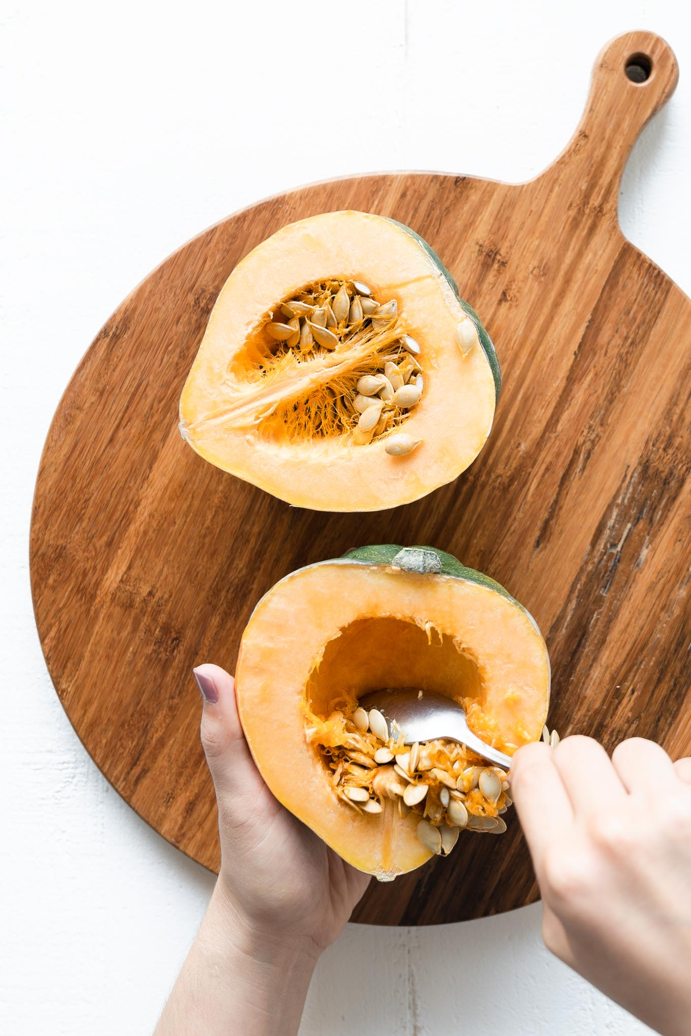 Scraping seeds out of acorn squash half with a spoon