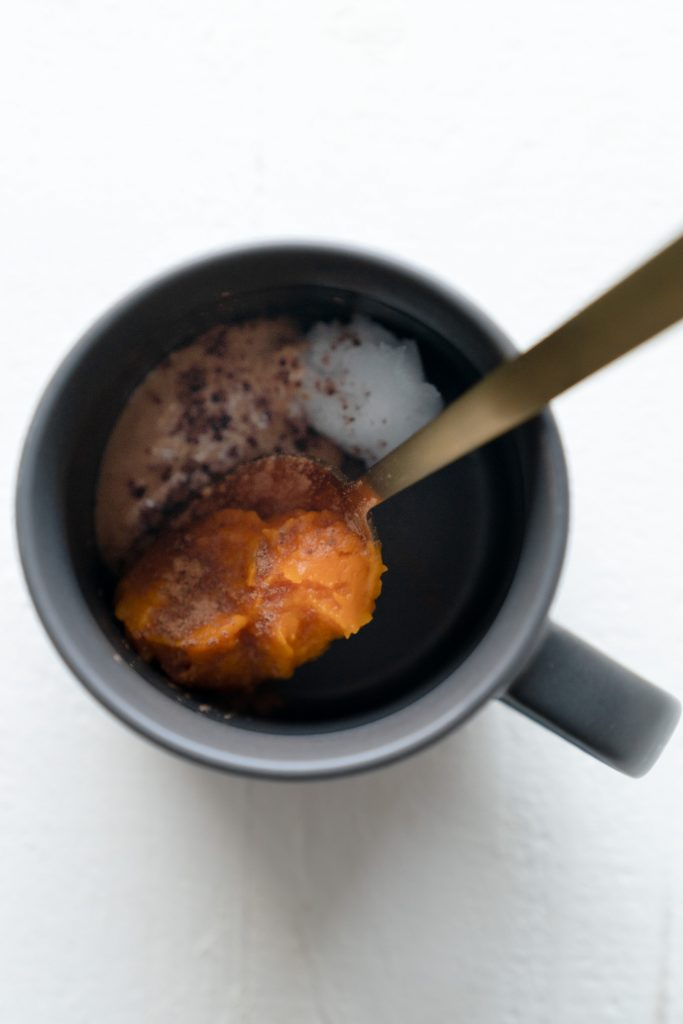 Top down shot of mug with pumpkin puree and gold spoon