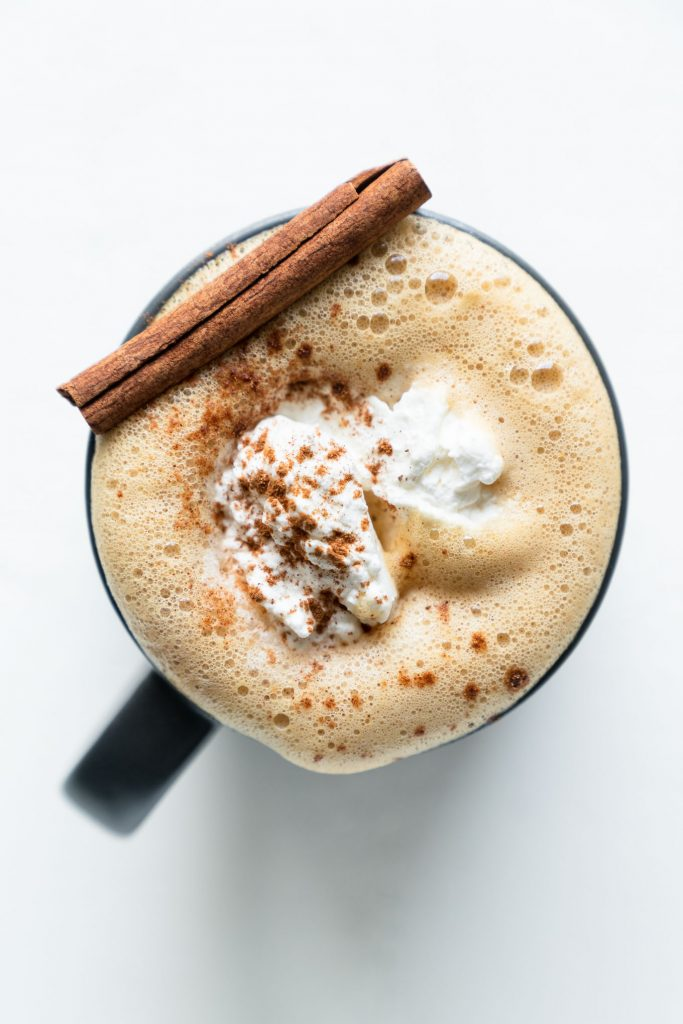Top down shot of pumpkin spice latte with cinnamon stick and whipped cream