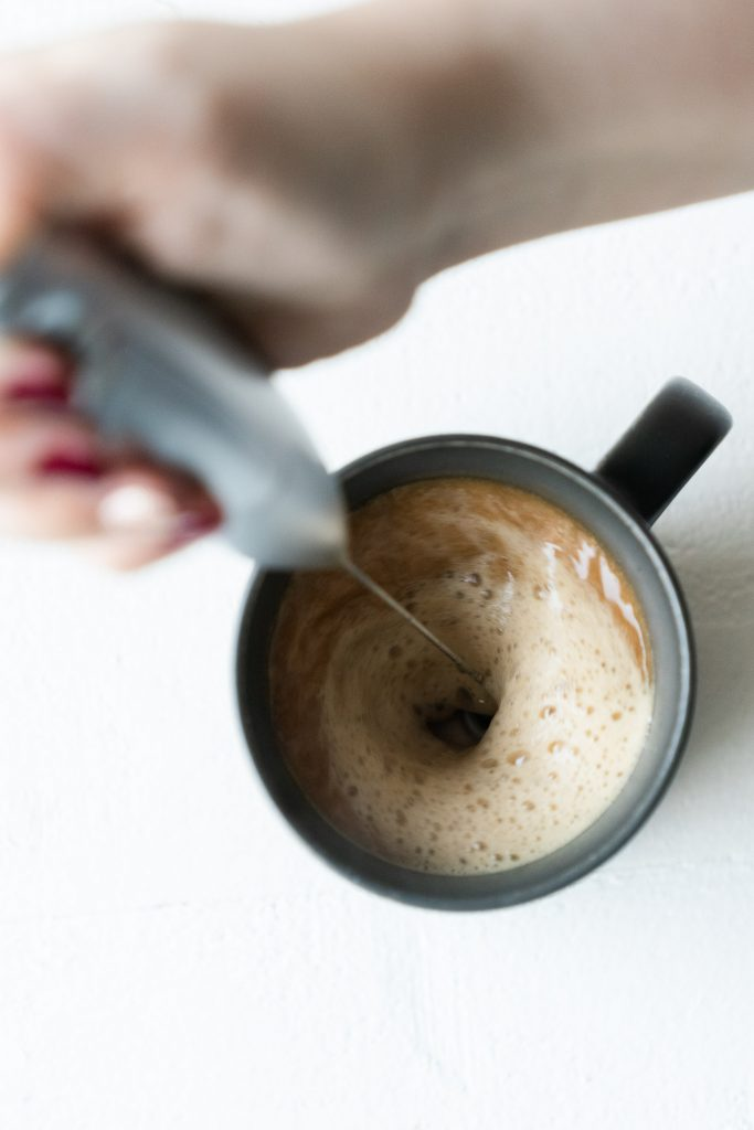 latte whisk in a black mug filled with coffee