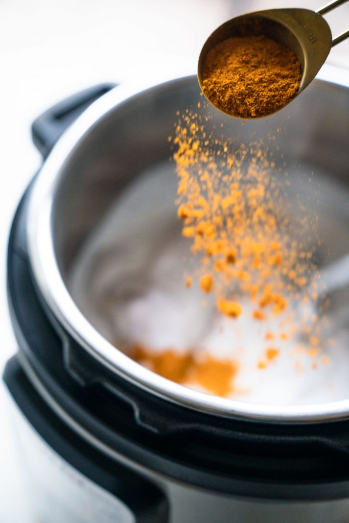 shaking curry powder over top coconut milk and chicken in instant pot