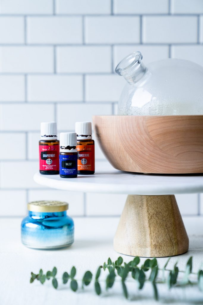 essential oil bottles shown with diffuser and blue candle