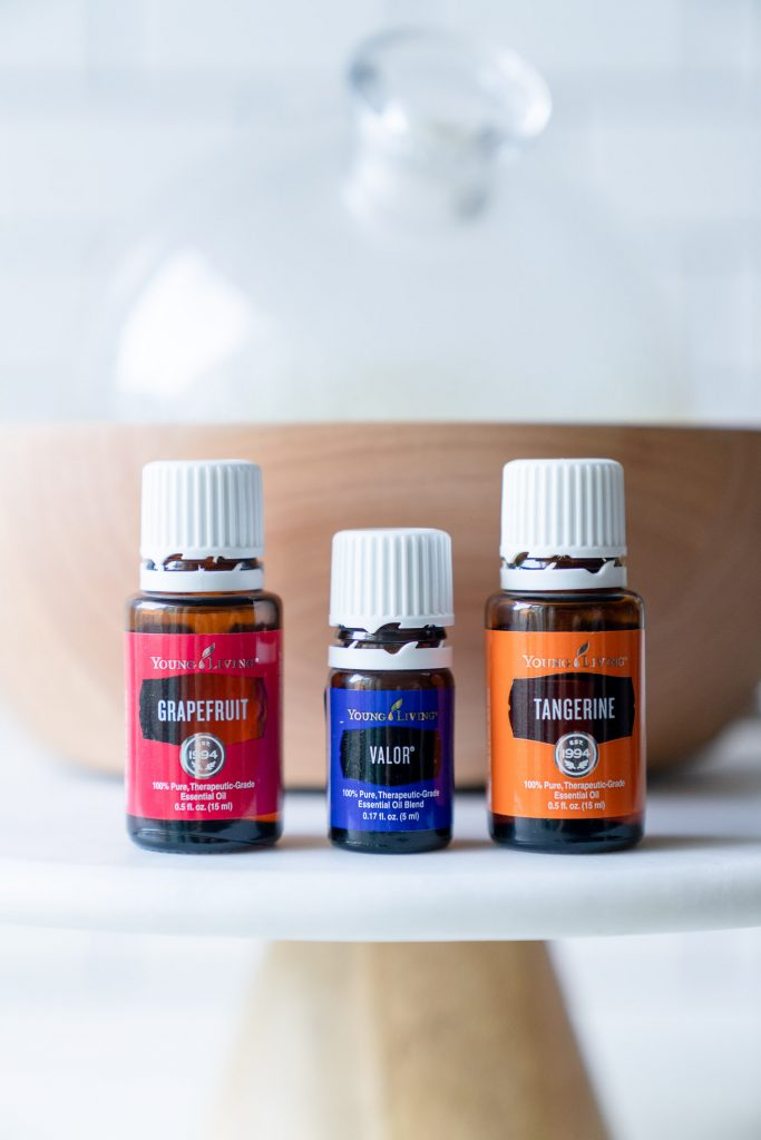 three essential oil bottles on a cake stand