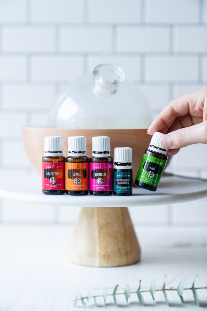 five essential oils with hand holding lime bottle