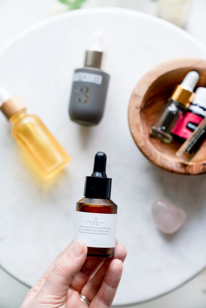 flatlay of bottles on table Best Clean Beauty Face Oils + Serums